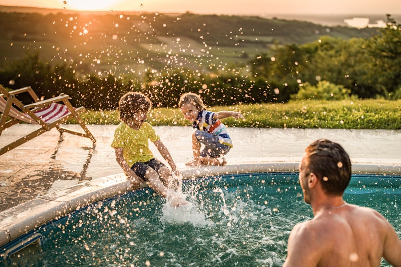 Father and Kids Splashing Poolside